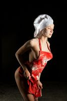 Sensual blonde female baker in red apron with flour