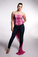 Young woman in pink corset, jeans, high heels with pink scarf