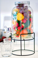 Glass jar beverage dispenser filled with fresh fruits and berries