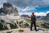 Nature photographer tourist with camera shoots while standing Italy Dolomites Alps.