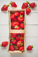 Wooden container with fresh red strawberries. Placed on white table.