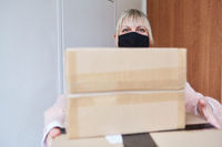 Frau mit Mundschutz und Paketen vor Wohnung