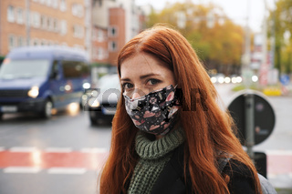 young woman wearing everyday cloth face mask outdoors in city raffic