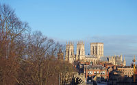 a view of york minster from the city walls with people and traffic crossing lendal bridge