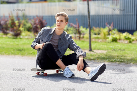 teenage boy sitting on skateboard on city street