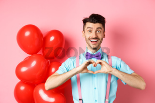Valentines day concept. Romantic guy looking happy and smiling, showing heart gesture to lover on special anniversary, standing on pink background