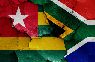 flags of Togo and South Africa painted on cracked wall