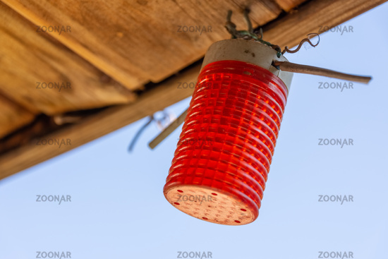 Red cylindrical light hanging from a ceiling