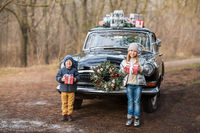 Siblings with gifts at vintage car in park