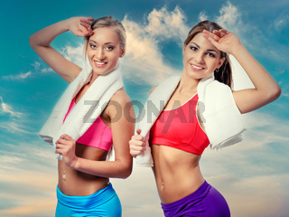Two beautiful girls after workout with towels on cloudy sky background