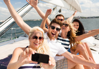 smiling friends sitting on yacht deck