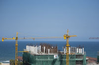 VIETNAM, DA NANG - April 10, 2019: Cranes and building construction site against blue sky and sea. Metal construction of unfinished building on construction. Tower Crane use for building of multi storage building.