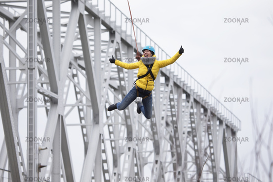 Belarus, Gomel, March 08, 2019. Jumping from the bridge to the rope.Ropejumping.Dangerous hobbies.Brave woman jumping from the bridge