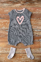baby bodysuit and socks on wooden table