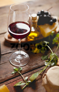 Glass of red wine with cheese and grapes