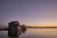 Little house on the lake at sunset