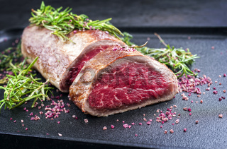 Fried dry aged beef fillet steak natural with herb and red wine salt offered as close-up on a black modern design tray