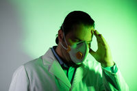 Medical doctor wearing a respiratory mask. Green light emergency and medicine crisis concept.