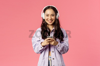 Portrait of attractive modern and stylish brunette korean, asian girl in headphones using mobile phone, listening music, made new playlist for going out, standing pink background