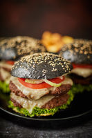 Black double cheeseburger with tomatoes and lettuce