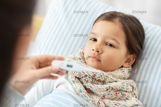 mother measuring temperature of sick daughter