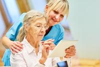 Pflegekraft hilft Seniorin mit Tablet Computer