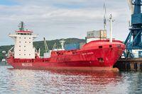 Cargo ship Sasco Angara Russian Sakhalin Shipping Company at pier commercial container terminal seaport. Portal crane unloading containers