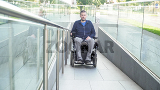 Front view of a man on electric wheelchair driving on a street. Accessibility concept