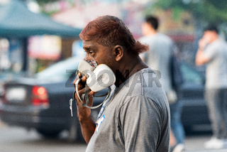 Notwendiger Atemschutz während des sprühens von Insektiziden in den Strassen von George Town