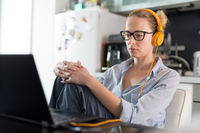 Female freelancer in her casual home clothing working remotly from her dining table in the morning. Home kitchen in the background.