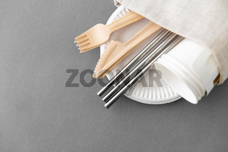 wooden forks, knives and paper cups on plate