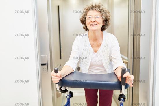 Seniorin mit Rollator im Fahrstuhl