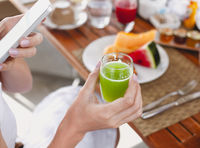 Crop woman drinking green juice and using smartphone