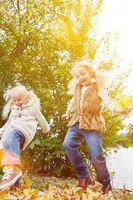Aktive Kinder spielen draußen im Herbst