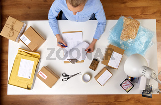 woman with clipboard and parcels at post office