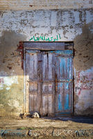 Closed abandoned wooden weathered door and shabby old grunge wall