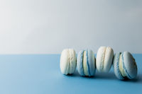 White and blue macaroons on the table, macaroons on blue background