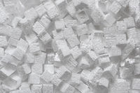 Many small cubes of white polystyrene, top view. Packaging material that creates protection for the goods inside the parcel during a during transportation