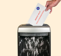 Absentee ballot or vote by mail envelope being shredded in an office shredder