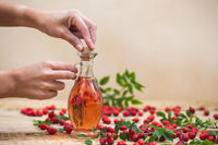 Two woman's hands closing flask with essential rosehip oil
