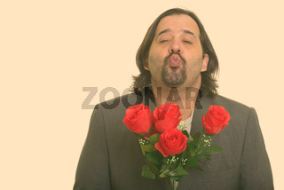 Fat Caucasian businessman puckering lips while holding red roses ready for Valentine's day