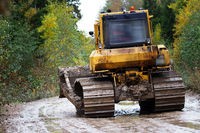 Crawler bulldozer rides on a dirt road
