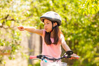 Girl riding on the bike outdoor and shows the trail