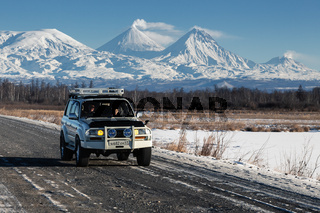 Japanese Sport Utility Vehicle Toyota Land Cruiser driving along road on background of beautiful winter landscape - active volcano on sunny day