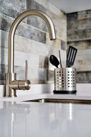 Faucet and sink on tiled wall background in modern domestic kitchen