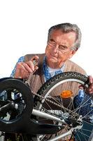 Senior repariert Fahrrad vor weißem Hintergrund