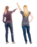 Back view of two pointing girl in sweater.