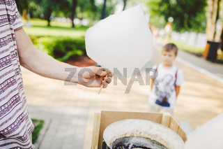 Theme is a family small business cooking sweets. Hands close-up A young male shopkeeper holding a merchant makes candy floss, fairy floss or Cotton candy in summer park