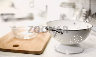 White colander and kitchenware on white kitchen