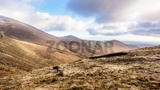 Beautiful valley in Mourn Mountains at autumn colours. Dramatic cloudy sky.